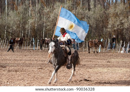 MENDOZA, ARGENTINA - MAY 25: A Gaucho with Argentinian flag riding a horse in exhibitions for Argentina 200 hundreds years anniversary. May 25, 2010 in Mendoza, Argentina - stock photo