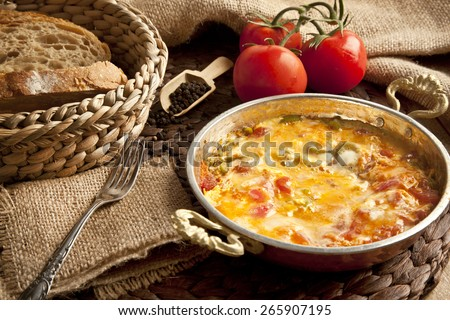 Menemen Turkish breakfast food egg, tomatoes and pepper in pan with concept background - stock photo
