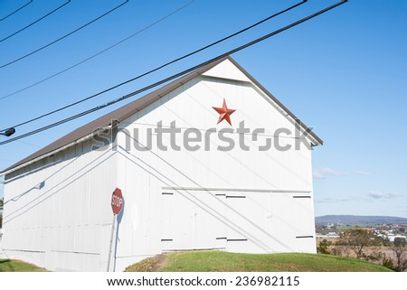 Mennonite red star on end of white farm shed. - stock photo