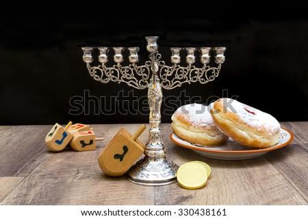 Menorah, donuts and dreidels for Hanukkah. Text-Israel - stock photo
