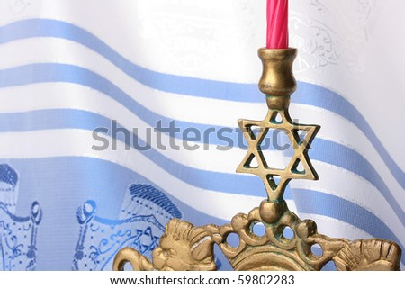 Menorah in front of a blue and white tallit. Add your text to the background.
