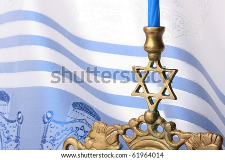 Menorah in front of a blue and white tallit. Add your text to the background. - stock photo