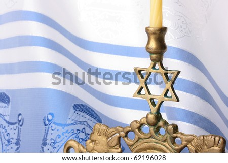 Menorah standing in front of a blue and white tallit. Add your text to the background. - stock photo