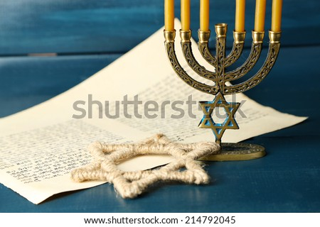 Menorah, star of David and page of Genesis book on wooden background - stock photo