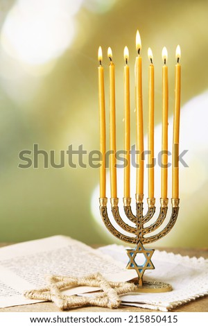Menorah, star of David and page of Genesis book on wooden table, on bright background - stock photo