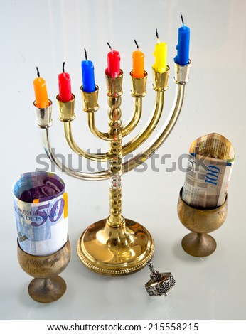 Menorah with candles and silver dreidel for Hanukkah celebration. - stock photo