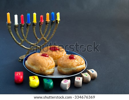 Menorah with candles, donuts with jelly and wood  dreidels with Hebrew caps letters for Hanuka celebration. - stock photo