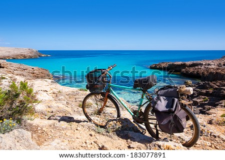 Menorca Cala des Talaier beach with aged grunge bicycle - stock photo