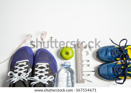Mens and kid fitness shoes with water measuring tape and apple. concept health family