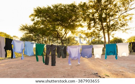 Mens and womens laundry drying on outdoor clothes line with pegs and sun streaming in behind - stock photo