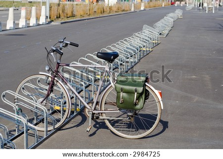 Mens bicycle standing in very long bicycle-stand at a parking lot.