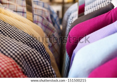 Mens clothes (shirts and sweaters) in a retail store - stock photo