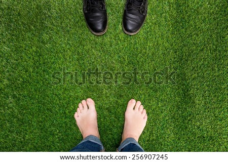Mens feet resting on green grass with standing opposite boots - stock photo
