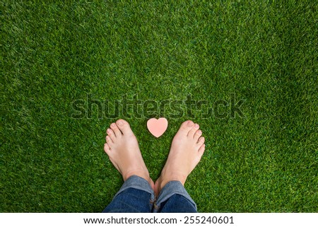 Mens feet standing on grass with small heart - stock photo