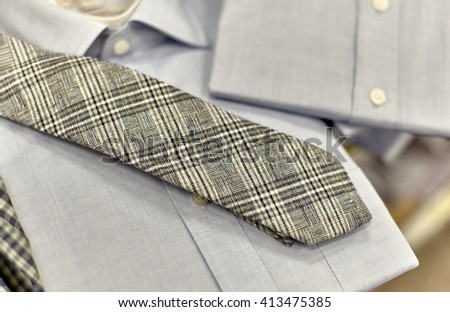 Mens folded dress shirt with necktie on shelf in department store with shallow depth of field - stock photo