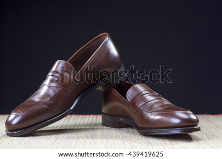 Mens Footwear Concepts. Pair of Stylish Brown Penny Loafer Shoes Placed on Straw Surface against Black.Horizontal Image Composition