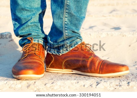 Mens legs in jeans and brown leather elegant  luxury shoes. Vibrant multicolored outdoors horizontal closeup image. - stock photo