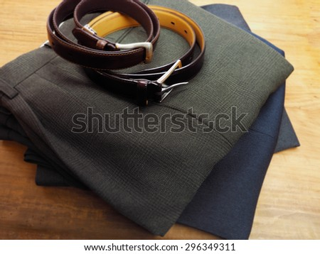 Mens trousers and belt on table ready for use. - stock photo
