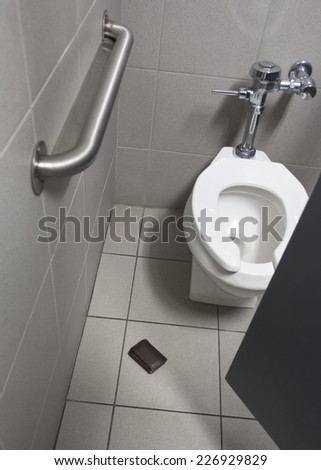 mens wallet on tile floor in stall of public restroom - stock photo