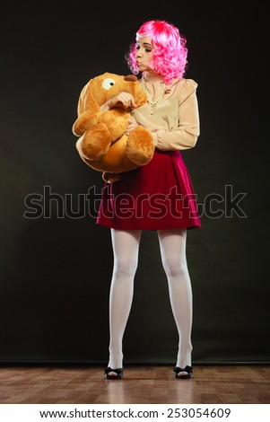 Mental disorder concept. Young childlike woman wearing like puppet doll and big dog toy standing dark black background - stock photo