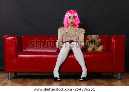 Mental disorder concept. Young childlike woman wearing like puppet doll sitting with teddy bear toy on red couch at home dark black background