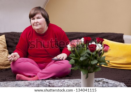 mentally disabled woman focused on music - stock photo