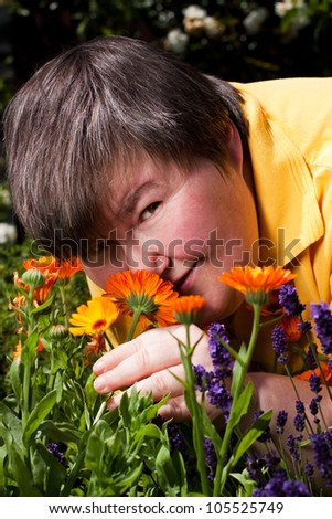 mentally disabled woman is in the garden and smell on flowers - stock photo