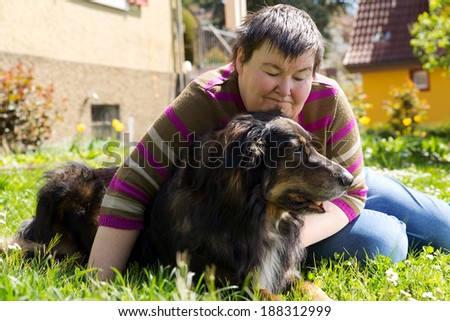 mentally disabled woman is lying with dog on a lawn - stock photo