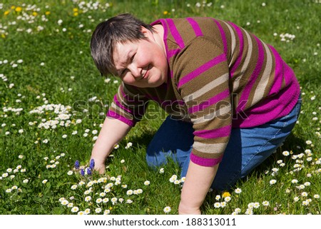 mentally disabled woman on a meadow - stock photo