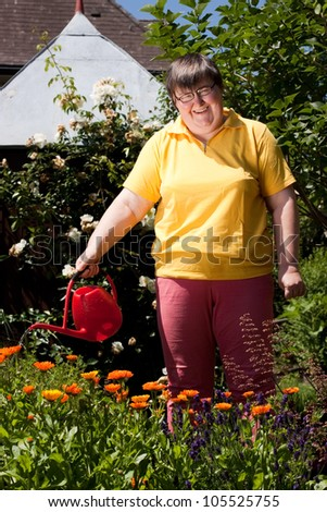 mentally disabled woman stands in the garden and  pours flowers - stock photo