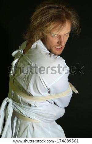 Mentally ill man in strait-jacket on black background - stock photo