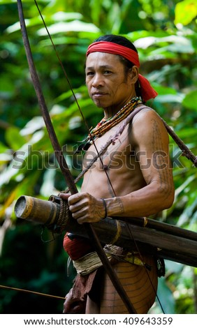 MENTAWAI PEOPLE, WEST SUMATRA, SIBERUT ISLAND, INDONESIA  16 NOVEMBER 2010: Man hunter Mentawai tribe with a bow and arrow in the jungle. 16 November, 2010. West Sumatra, Siberut island, Indonesia.