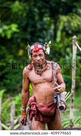 MENTAWAI PEOPLE, WEST SUMATRA, SIBERUT ISLAND, INDONESIA â?? 03 OKTOBER 2011: Man hunter Mentawai tribe with a bow and arrow in the jungle. 03 October, 2011. West Sumatra, Siberut island, Indonesia. - stock photo