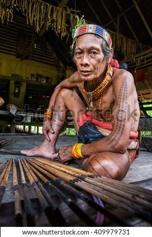MENTAWAI PEOPLE, WEST SUMATRA, SIBERUT ISLAND, INDONESIA â?? 03 OKTOBER 2011: Men Mentawai tribe prepare arrows for hunting. 03 October, 2011. West Sumatra, Siberut island, Indonesia. - stock photo