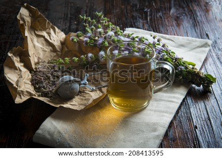 Mentha pulegium infusion on a wooden table - stock photo