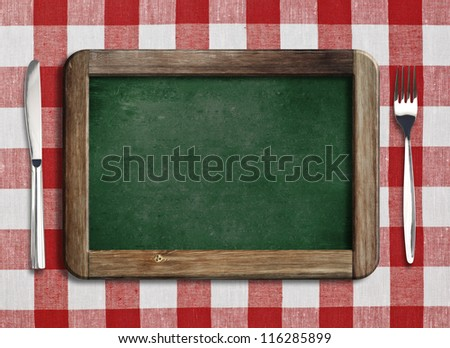Menu blackboard lying on table with knife and fork - stock photo