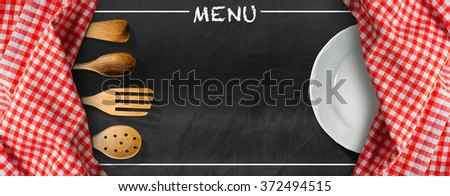 Menu - Blackboard with Kitchen Utensils and Plate / Blackboard with red and white checkered tablecloth, text Menu, wooden kitchen utensils and white empty plate. Template for a food menu - stock photo