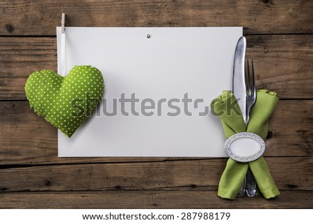 Menu card with a green heart and white polka dots plus cutlery and napkin for a background. - stock photo
