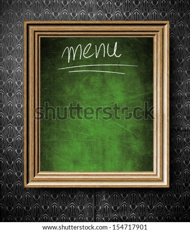 Menu chalkboard with copy-space in old wooden frame on vintage wall - stock photo