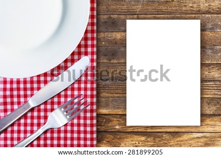 Menu concept. White plate, fork and knife placed on old wooden table with red checked tablecloth and empty place for text. Top view. - stock photo