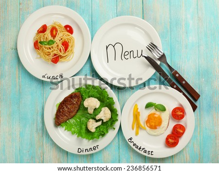 Menu of day. Plates with food on table - stock photo