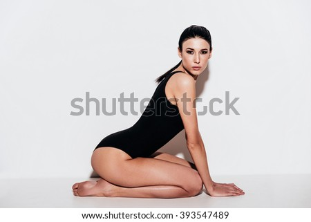 Meow! Side view of beautiful young woman in black swimsuit looking at camera while sitting against white background - stock photo