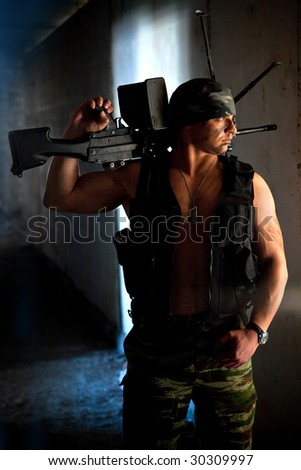 Mercenary with submachine gun on the ruined building background