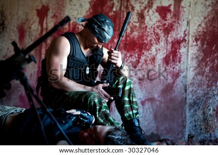 Mercenary with the gun near a dead body on the bloody wall background.