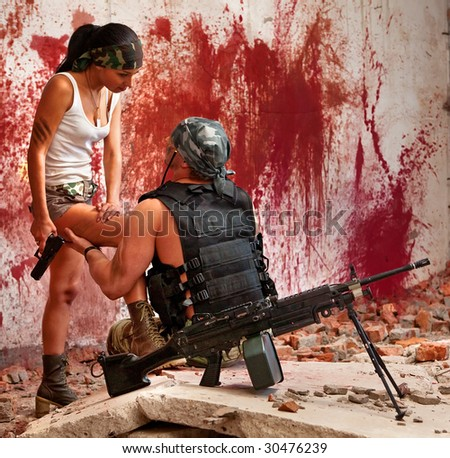 Mercenary with the submachine gun and sexy girl on the bloody wall background