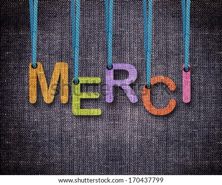 Merci Letters hanging strings with blue sackcloth background. - stock photo