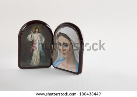 Merciful Jesus and Our Lady of Medjugorje, the Blessed Virgin mary, images in a wooden rounded case isolated on white backgrounds with shady reflection on white table. - stock photo