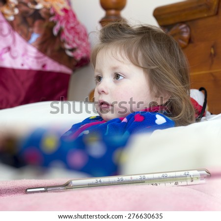 Mercury thermometer showing high temperature and a little sick girl in bed - stock photo
