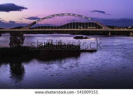 Merida, November 2012. Lusitania bridge over Guadiana river. Santiago Calatrava architect, built in 1991 on concrete and steel. 480 meters. 190 meters of  arch. People walking. - stock photo