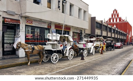 Merida, Yucatan Mexico, January 22, 2015: Horse carriages wait for passengers on a city street in Merida Mexico.                                - stock photo